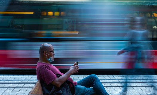 A long exposure photograph of a man sitting at a transport stop, as a vehicle goes by in background, blurred. The man is on his phone, and has a face mask pulled under his chin.